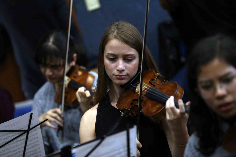 Una joven de la orquesta sinfonica tocando el violin