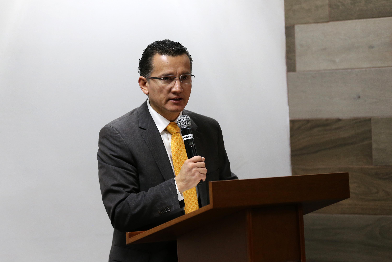 Doctor Eduardo Gómez Sánchez, coordinador de carrera, en podium del evento y con micrófono en mano, haciendo uso de la palabra.