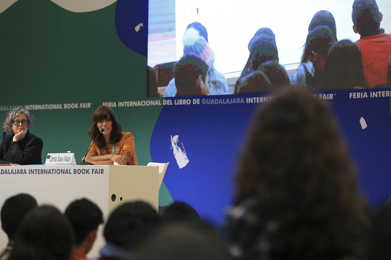 Camila Sosa durante la conferencia y atras una proyeccion de video