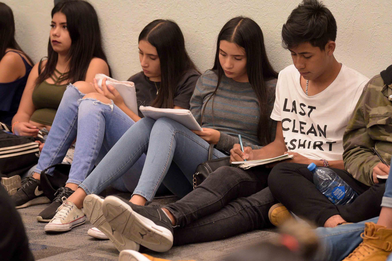 Grupo de estudiantes de bachillerato, sentados en el suelo, haciendo anotaciones en su cuaderno.