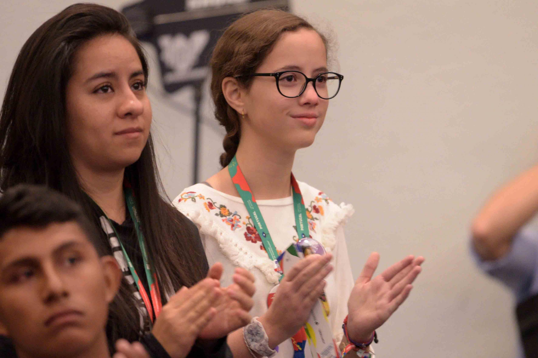 Mujeres estudiantes de bachillerato aplaudiendo.