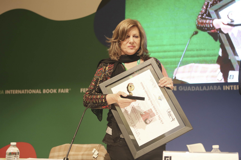 La Sociologa, profesora e investigadora de la Universidad Autónoma Metropolitana, doctora Graciela Bensusán; mostrando la Presea especial Demetrio Vallejo Martínez, que le fue entregada durante la ceremonia.