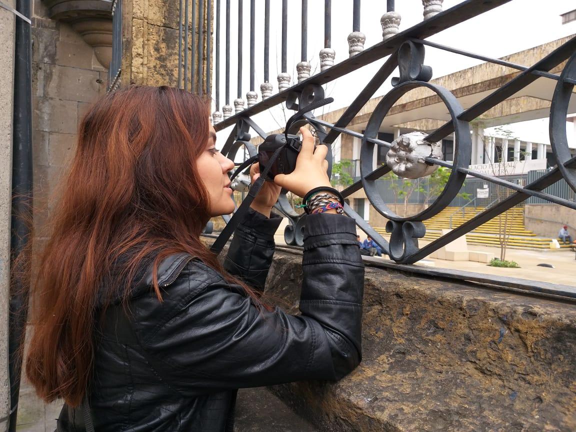Joven mujer tomando una fotografía a través de un enrejado.