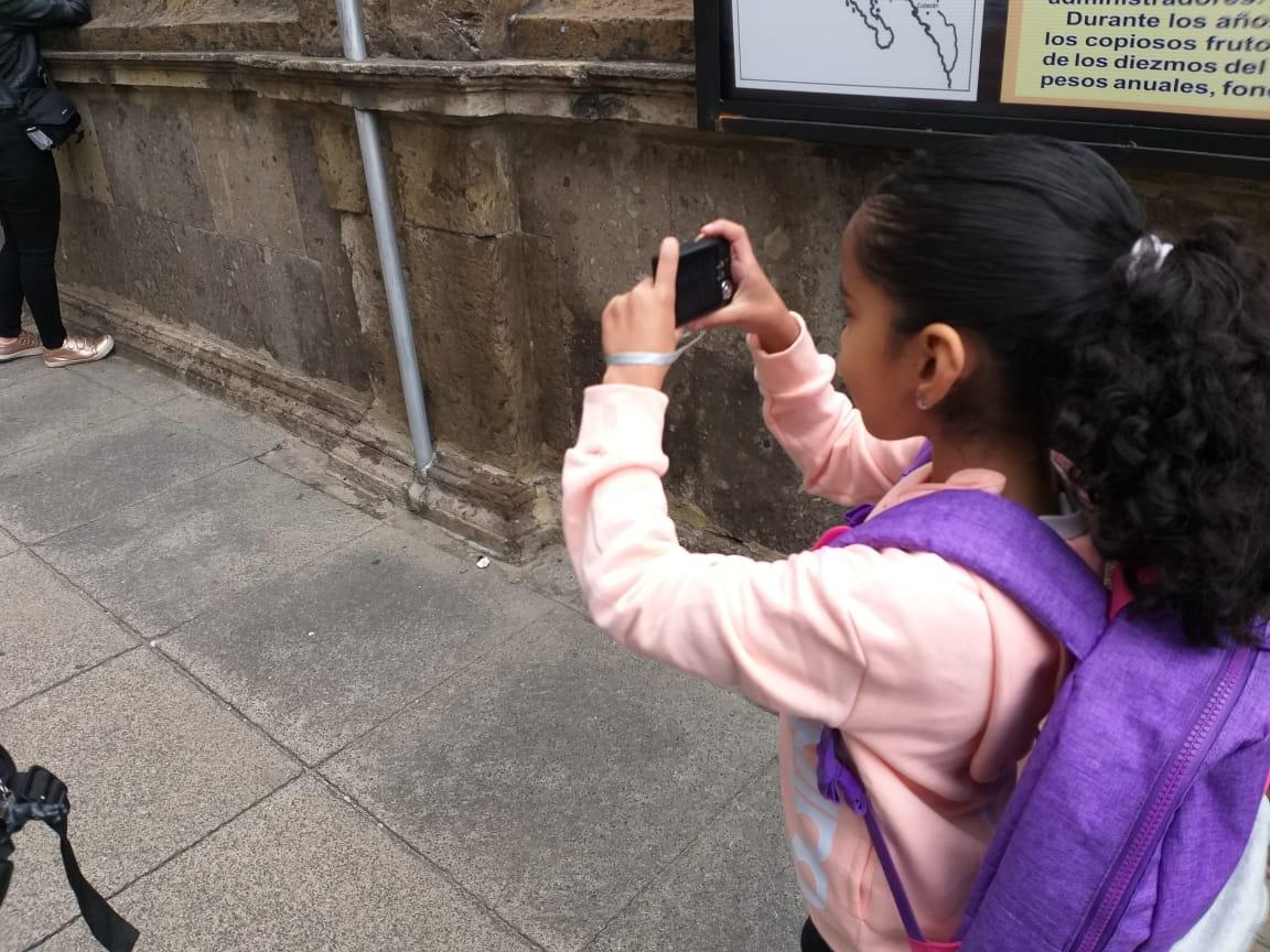 Niña pequeña tomando una fotografía a la calle.