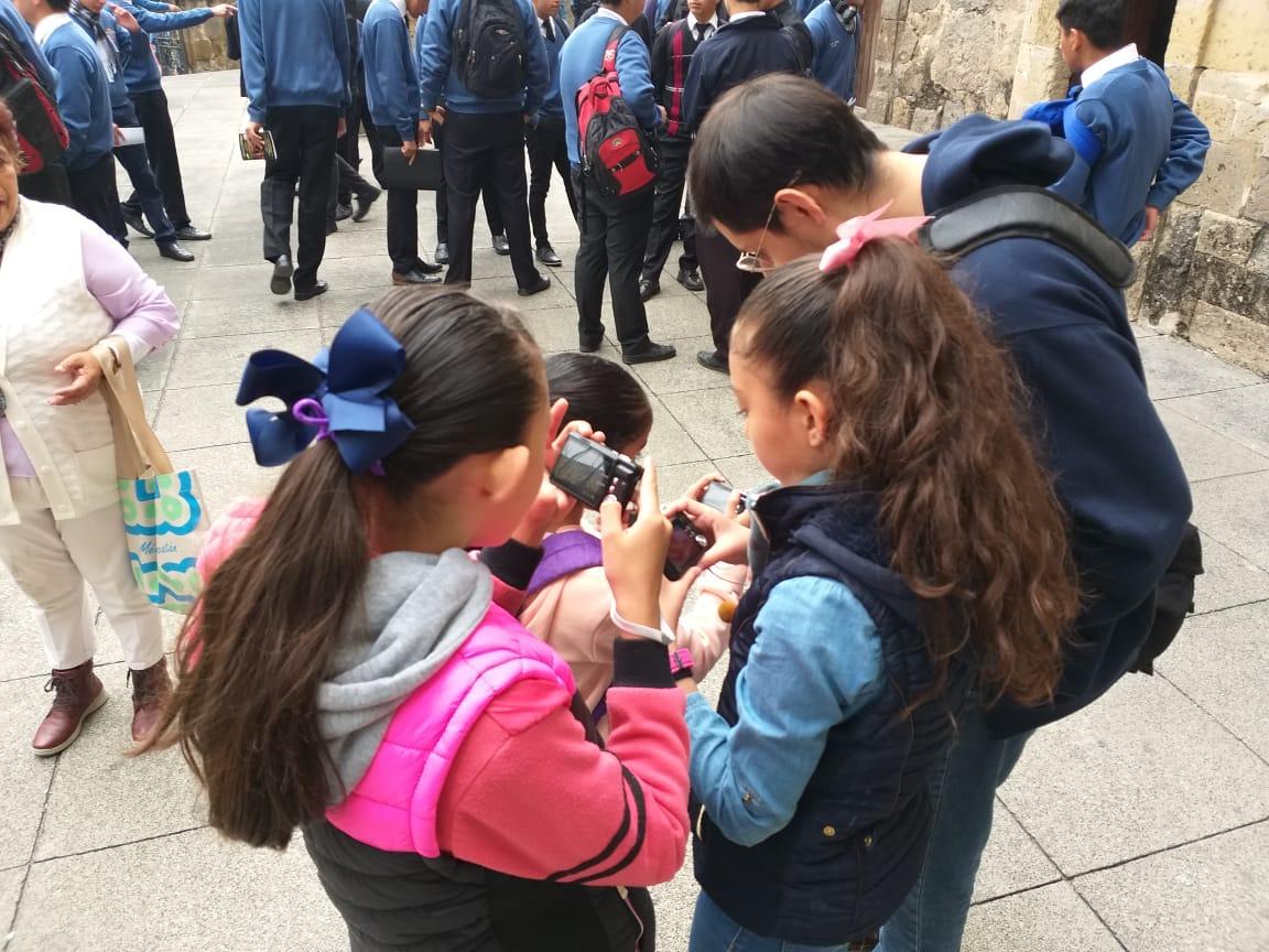 Un grupo de niños viendo las fotografías que han tomado con sus cámaras fotográficas.
