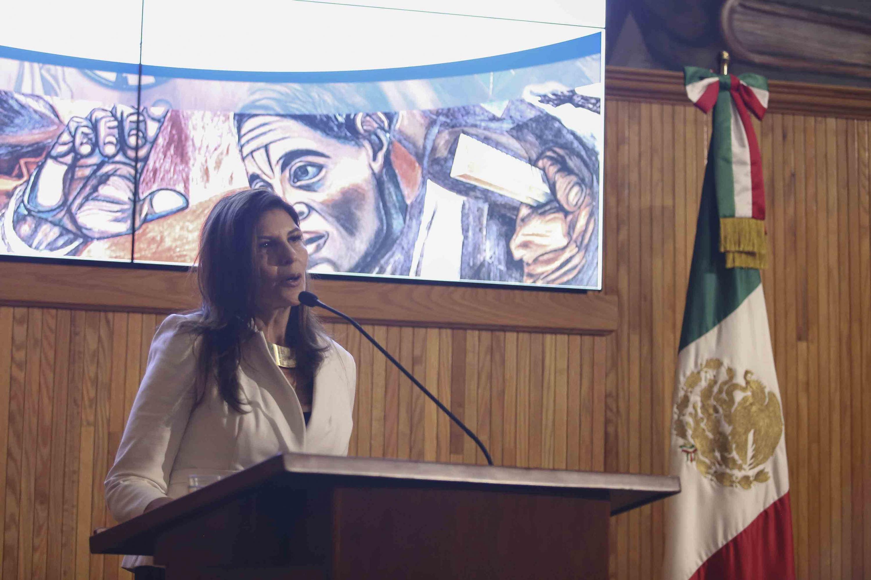 Raquel Partida Rocha dirigiendo unas palabras al público, desde el podio.
