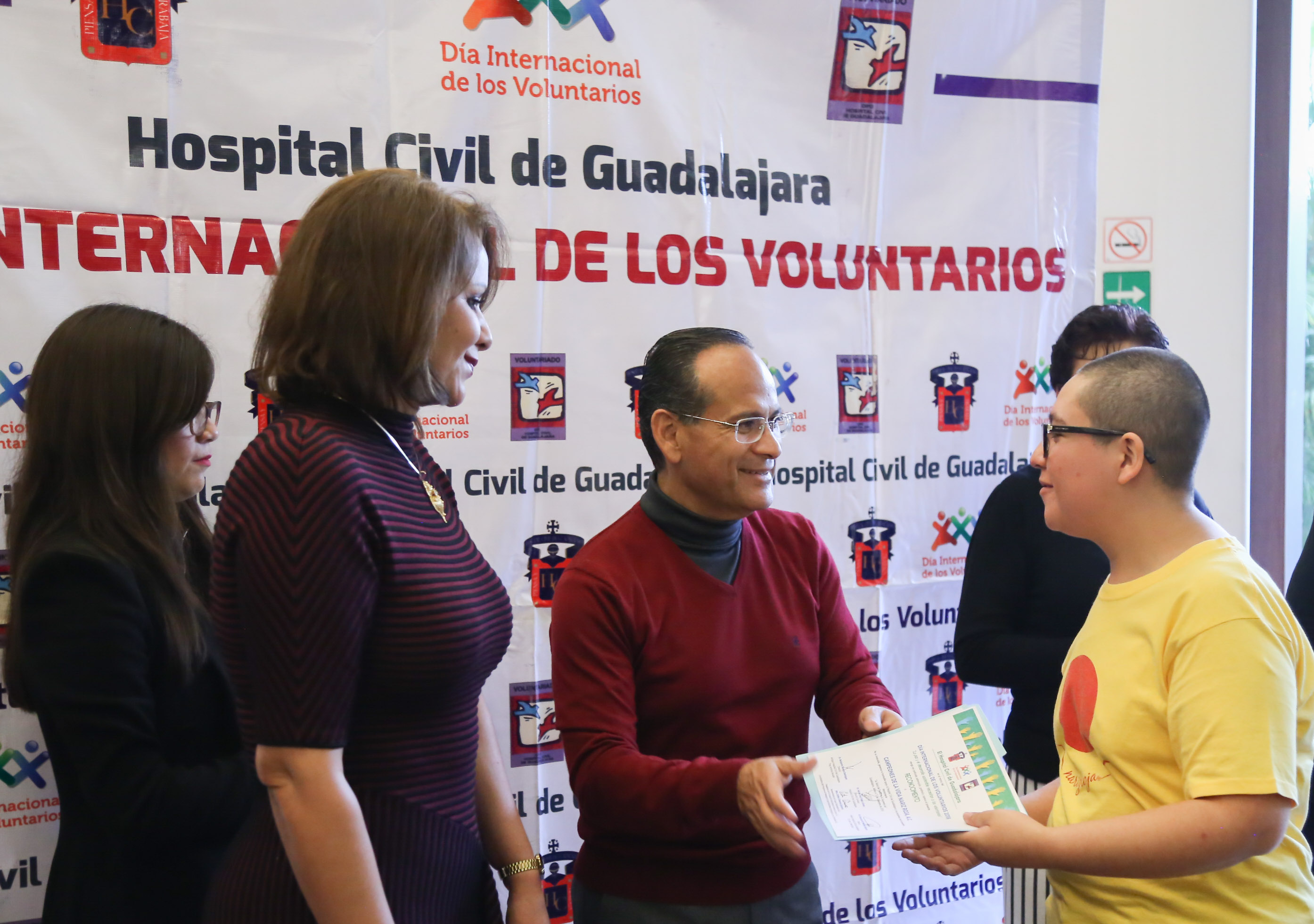 El doctor Héctor Raúl Pérez Gómez con integrantes de  hace entrega del reconocimiento a un voluntario de la asociacion CAMPEONES DE VIDA NARIZ ROJA