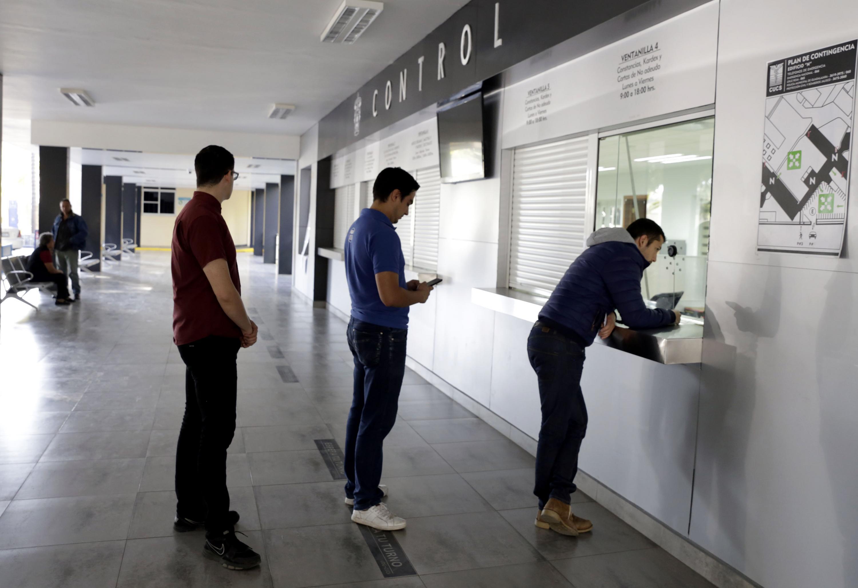 Aspirantes a la UdeG, haciendo fila en ventanilla de Control Escolar de un centro universitario, para entregar documentación.