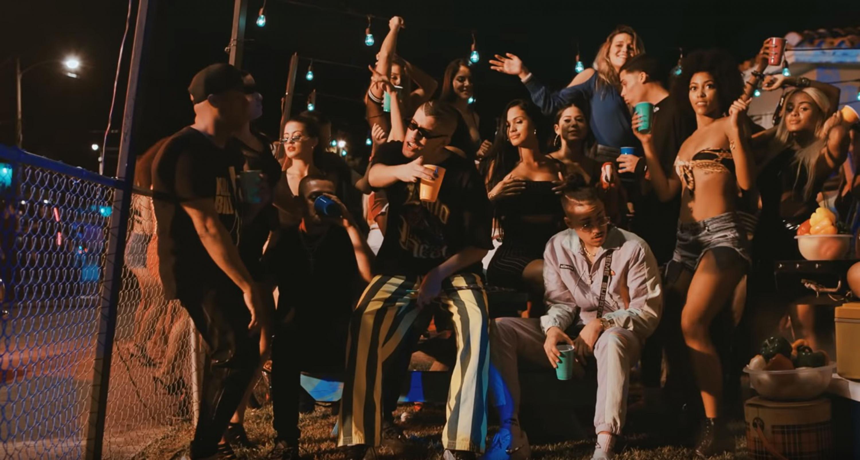Escena de un video musical de reguetton donde el cantante aparenta estar en una fiesta callejera