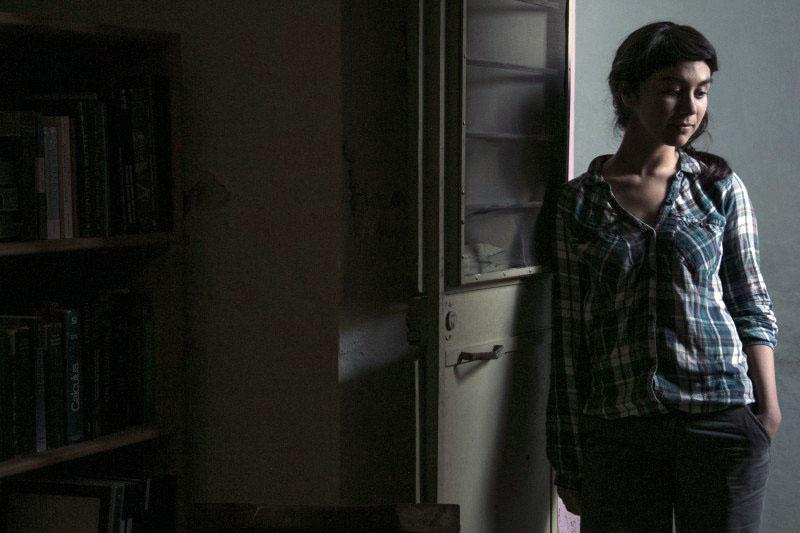 """Partes de la escena de la película """"Los años azules"""", donde una mujer jóven vestida casualmente, se encuentra pensativa y recargada en la puerta de entrada del cuarto de una casa antigua."""
