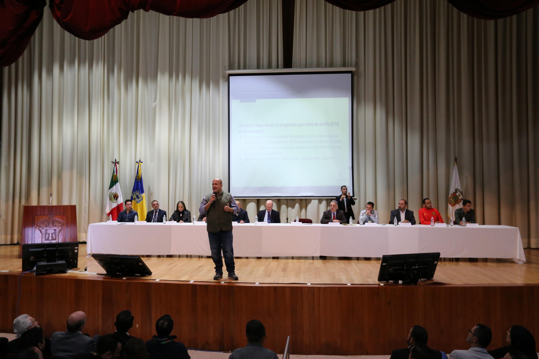 El gobernador Enrique Alfaro hablando al publico de pie adelante de la mesa de presidium