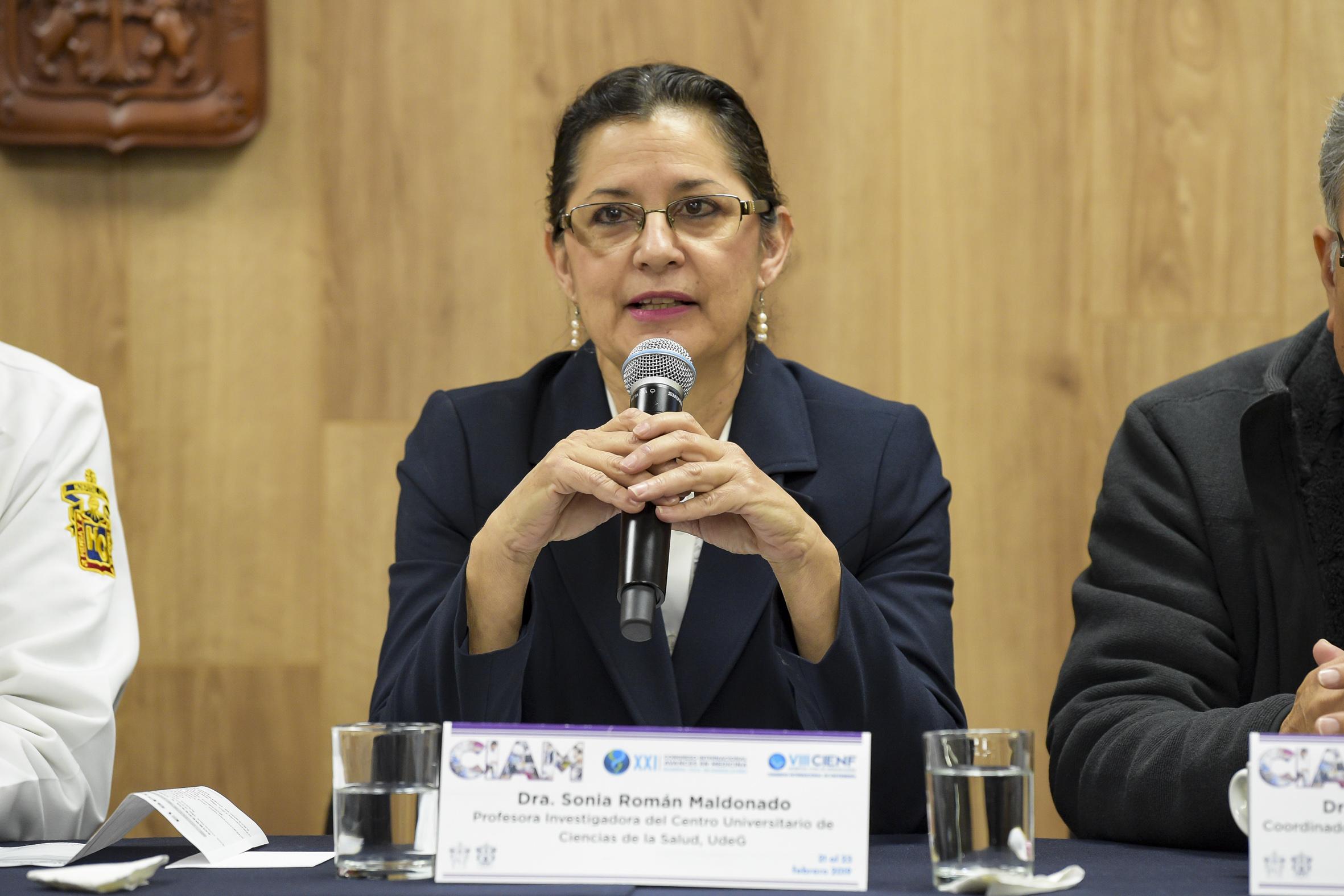 Profesora investigadora del Centro Universitario de Ciencias de la Salud (CUCS), doctora Sonia Román Maldonado, hablando frente al micrófono durante la rueda de prensa