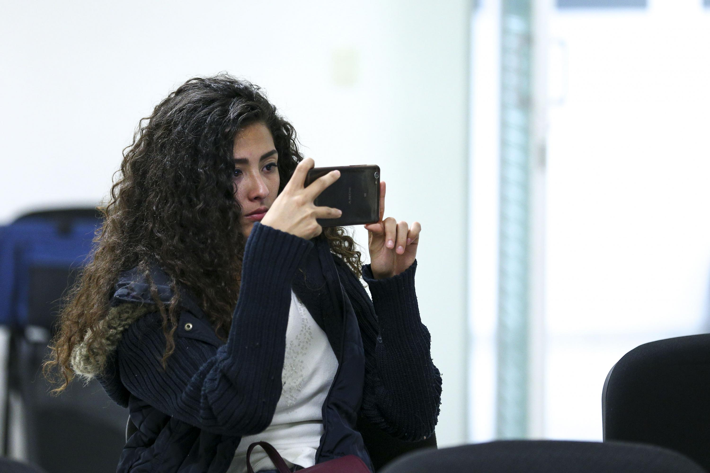 Mujer joven tomando vídeo con su celular durante la conferencia magistral