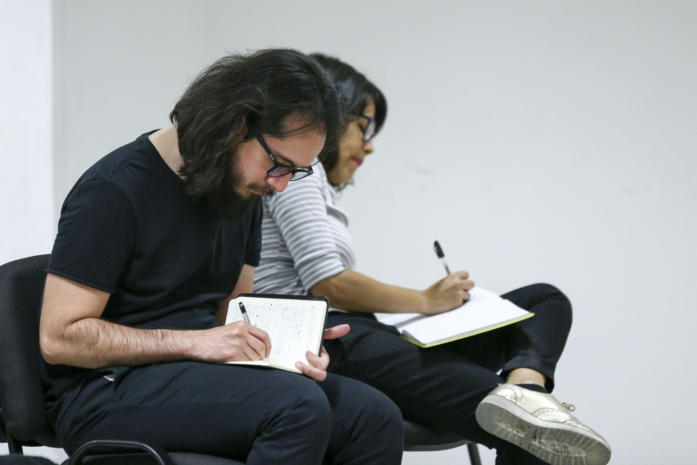 Publico asistente haciendo anotaciones durante la conferencia magistral