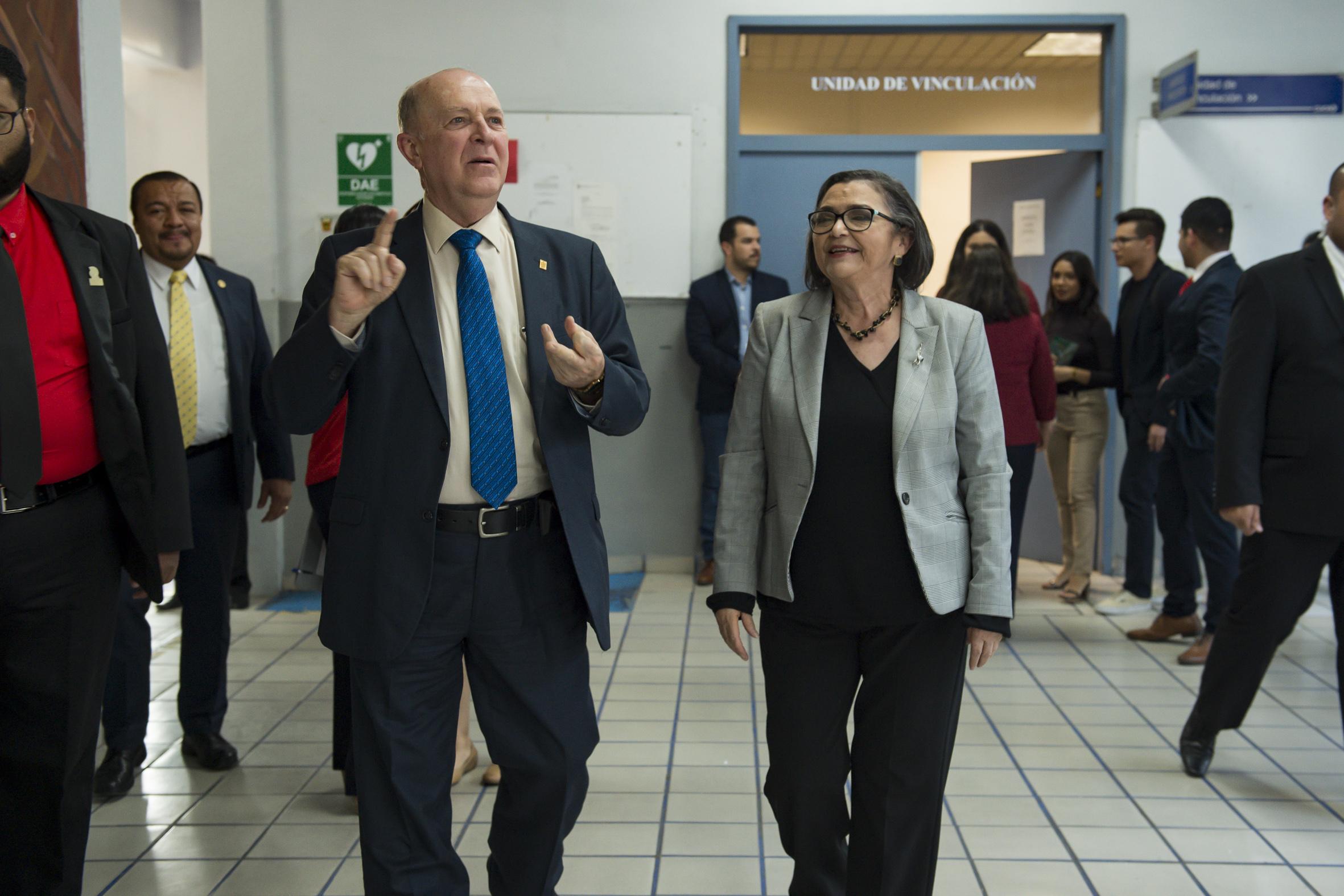 Rector General de la Universidad de Guadalajara, doctor Miguel Ángel Navarro Navarro y la doctora Ruth Padilla Muñoz caminando en los pasillos del CUCEI