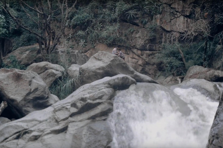 """Escena de la película documental """"La herencia del viento"""" en donde una mama baña a un niño en un arroyo"""