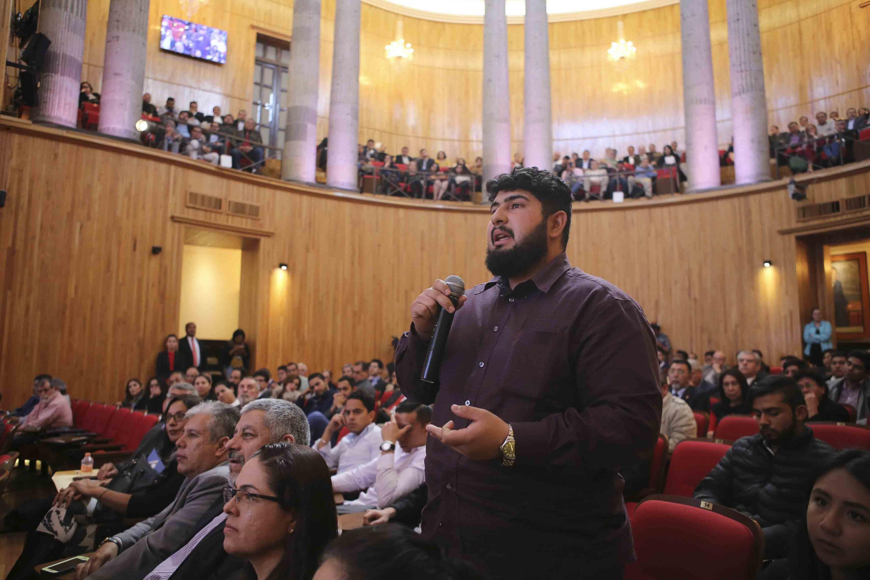 Miembro del Consejo General Universitario hablando frente al micrófono