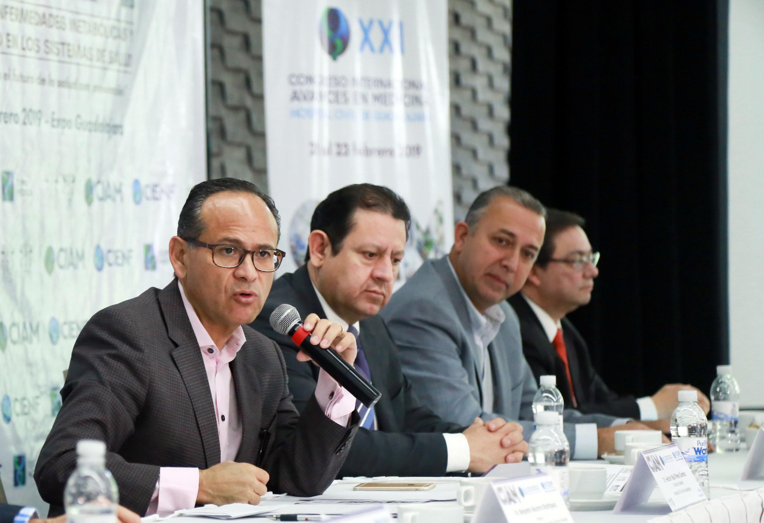 El doctor Héctor Raúl Pérez Gómez  hablando al micrófono desde la mesa del presidium