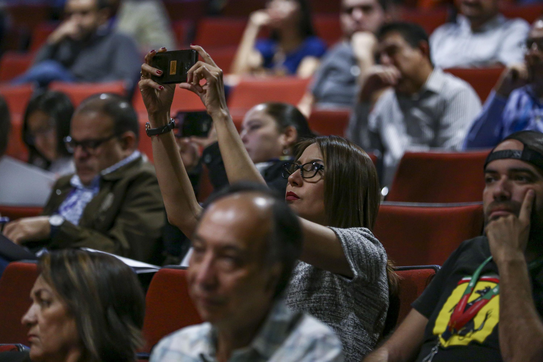 Una mujer del publico toma una foto con su telefono inteligente