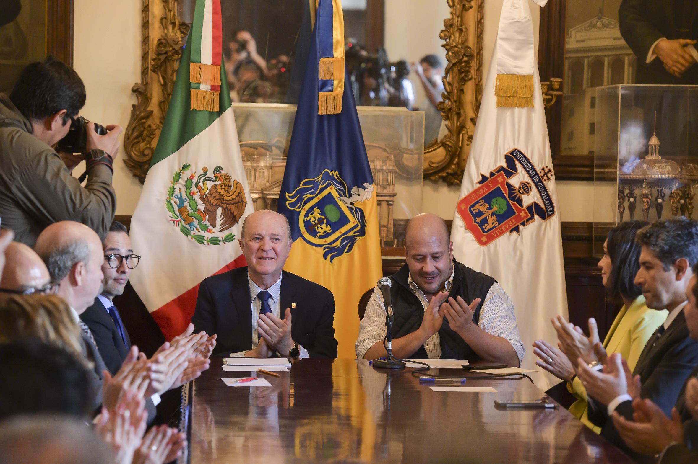 El rector General y el Gobernador del Estado de Jalisco sonríen y aplauden en la reunión de firma del convenio