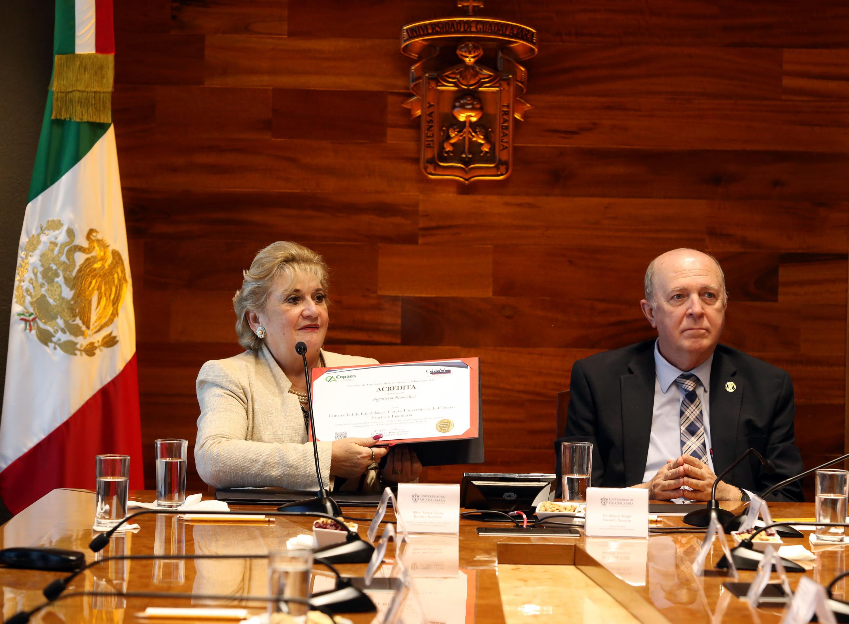 La maestra María Elena Barrera Bustillos muestra el certificado durante la presentación