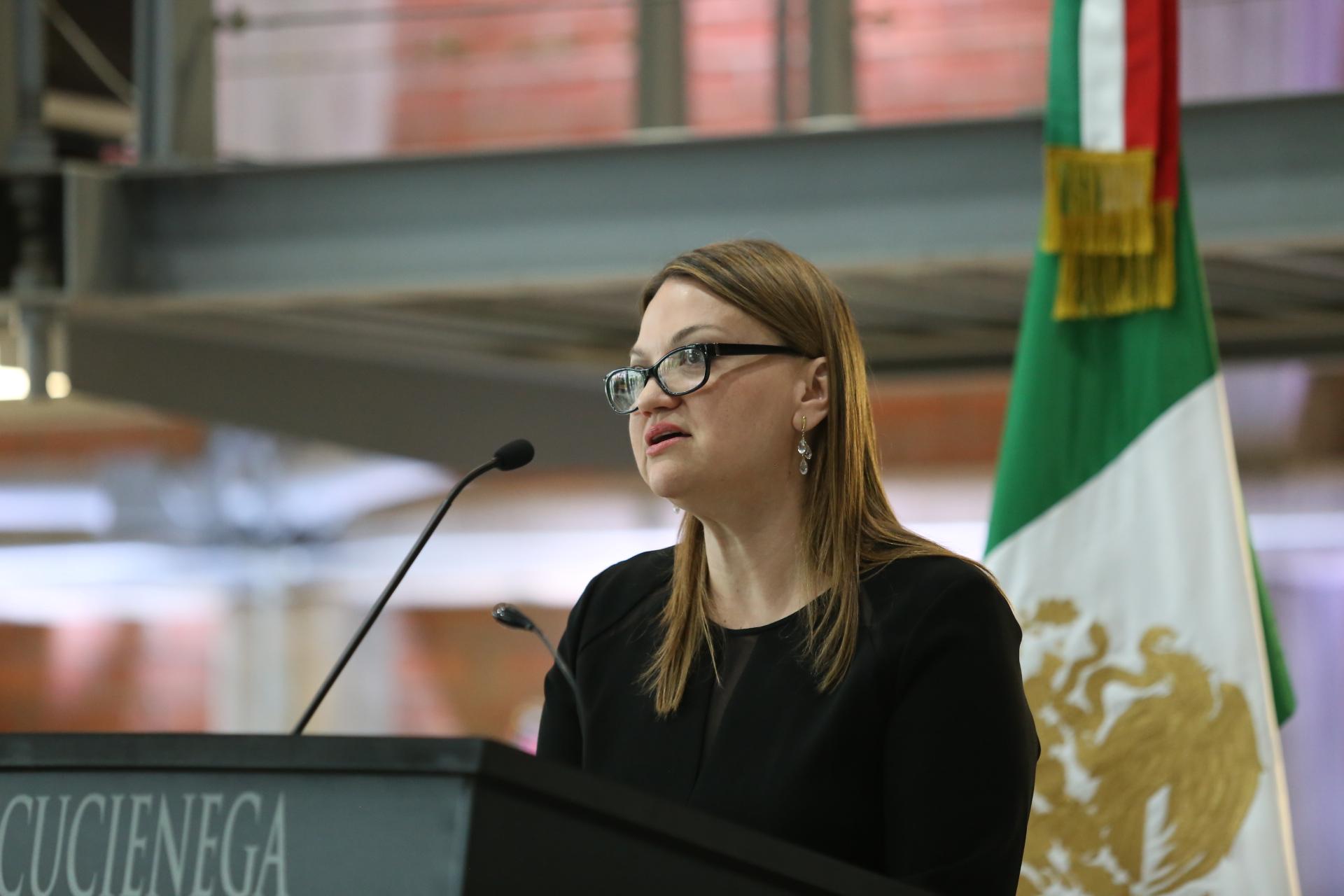 maestra María Felícitas Parga Jiménez, Rectora del Centro Universitario de la Ciénega hablando al micrófono desde el podium del auditorio