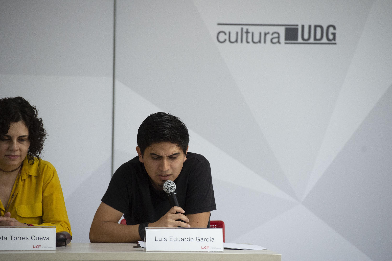 El poeta Luis Eduardo García habla al publico desde la mesa de presentación