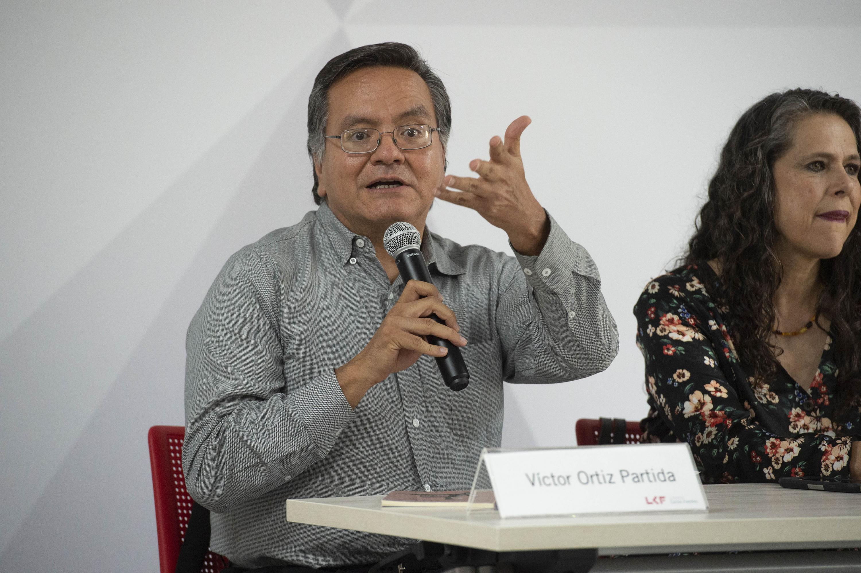 Victor Ortiz Partida hablando al publico desde la mesa de presentacion del libro de poemas