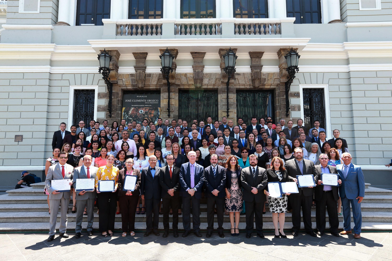 Toma de fotografía grupal de autoridades de la Universidad de Guadalajara y representantes acreditadores de los programas, fuera del Museo de la Artes (MUSA)