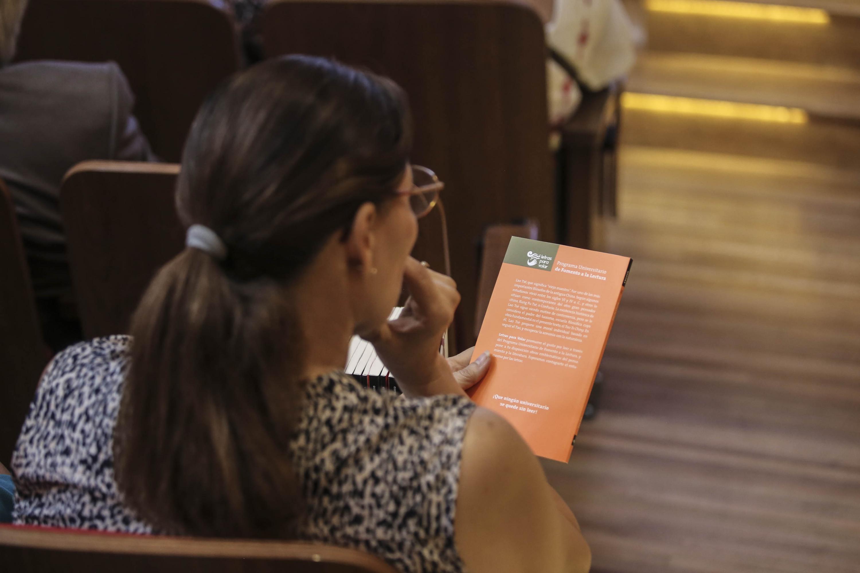 """Asistente a la ceremonia, leyendo un libro del Programa Universitario de Fomento a la Lectura """"Letras para volar"""""""