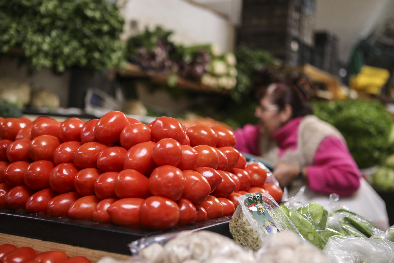 Señora comprando en un puesto de verduras de un mercado local
