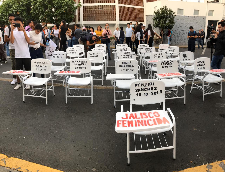 Decenas de butacas pintadas de blanco con nombres de estudiantes desaparecidos y estudiantes de la Universidad de Guadalajara frente a la sede de la Fiscalía General del Estado, ubicada en la Calzada Independencia