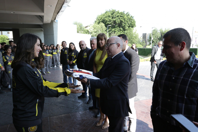 Secretario General de  la Universidad de Guadalajara (UdeG), maestro José Alfredo Peña Ramos, haciendo entrega de la bandera de la UdeG,  a la atleta Alely Hernández Martínez
