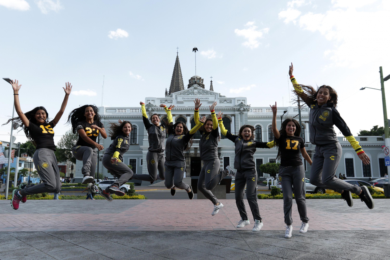 Atletas que participarán en la Universiada saltando en la explanada del edificio de rectoria