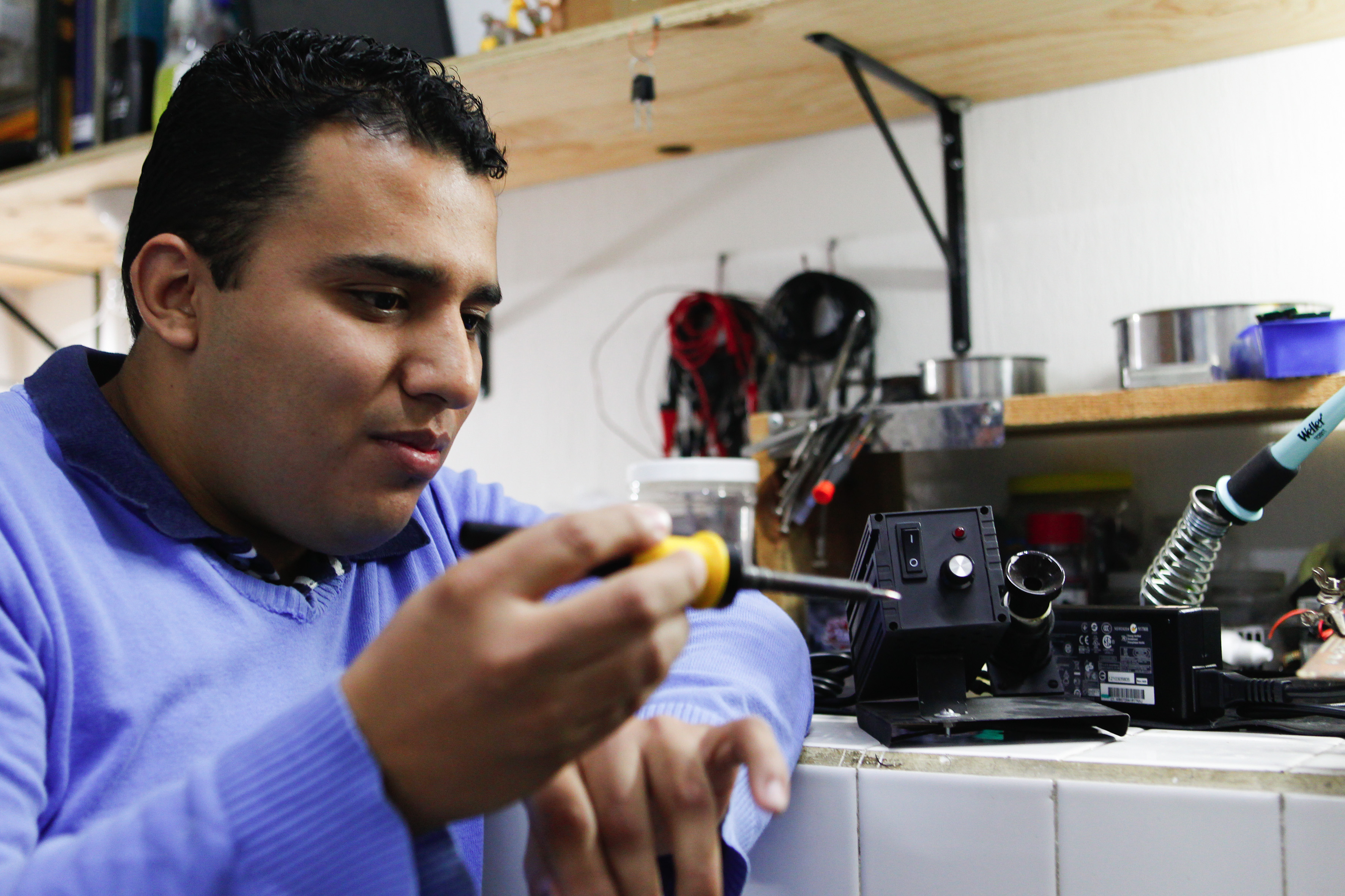 Maestro Ernesto Edgar Mazón Valadez, profesor del Laboratorio de Biofísica del CUCiénega y desarrollador del aparato, portando un cautín de inducción magnética autorregulable, alimentado por una fuente de radiofrecuencia de bajo voltaje.