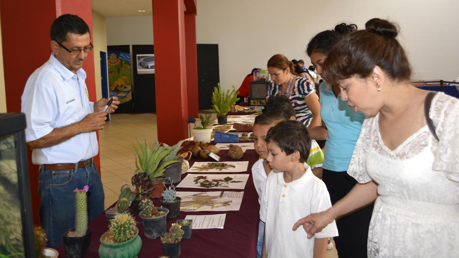 Niños y adultos participando exposición biológica del CUCSUR