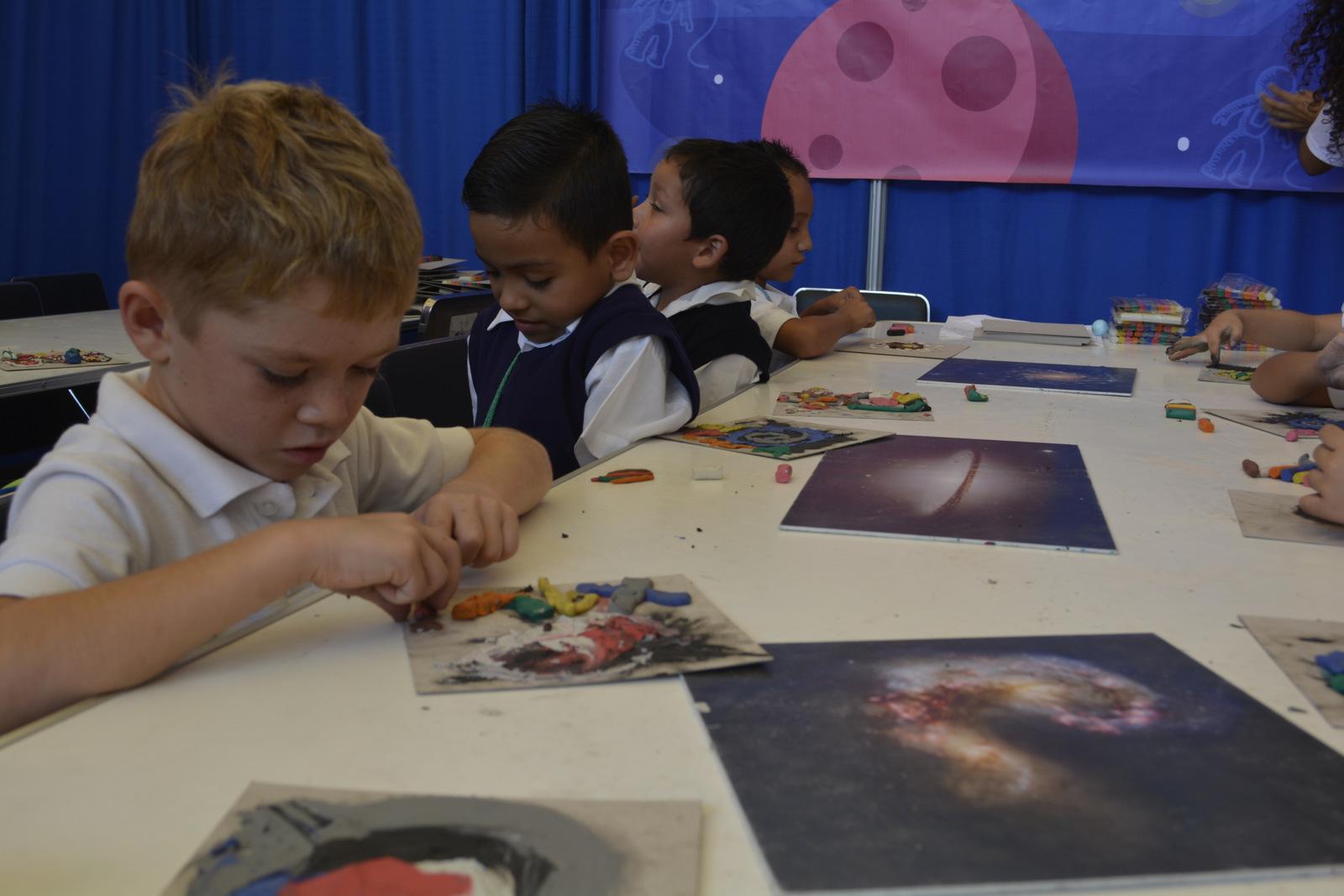 Niños pequeños de primaria, en taller de plastimasa de galaxias, tratando de hacer una de ellas.