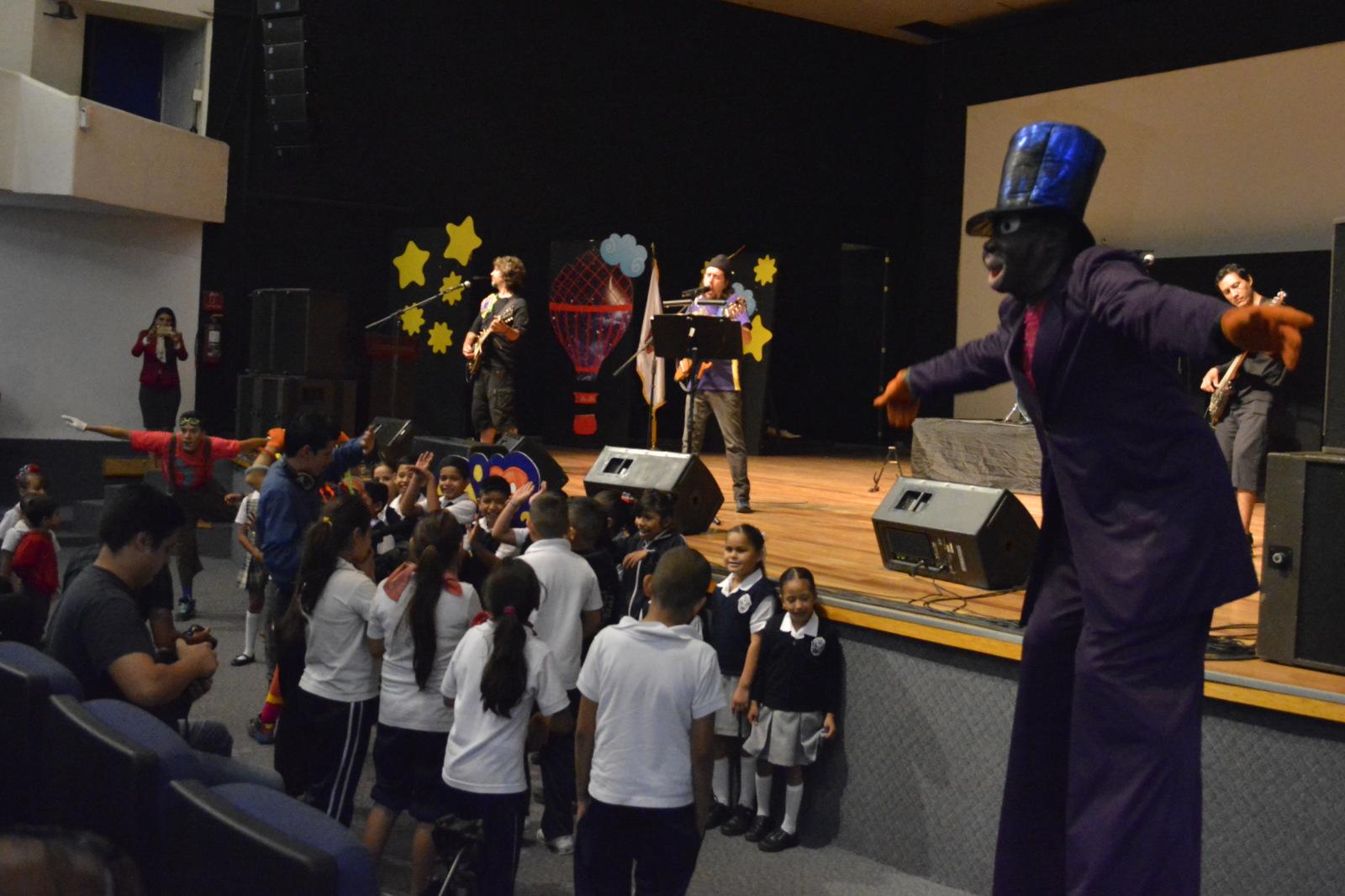 Grupo de niños de escuelas de Autlán y alrededores, disfrutando de un espectáculo de música y de eventos con personajes de un negrito en zancos y un payaso, dentro del auditorio del Centro Universitario.