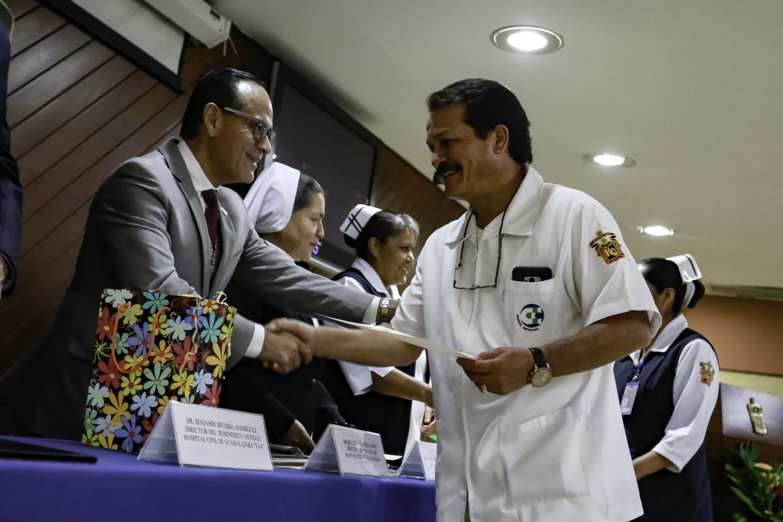 Enfermero recibiendo reconocimiento de parte del doctor Héctor Raúl Pérez Gómez, director general del Hospital Civil de Guadalajara
