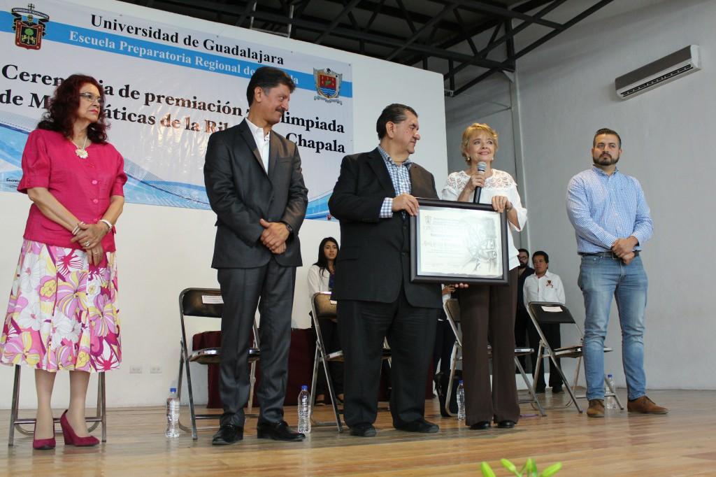 Juan Ramón Álvarez López y por el secretario de Educación Jalisco, Francisco de Jesús Ayón López dando reconocimiento a la maestra Pilar Morfin Heras, docente de la Preparatoria y miembro fundador del comité organizador.