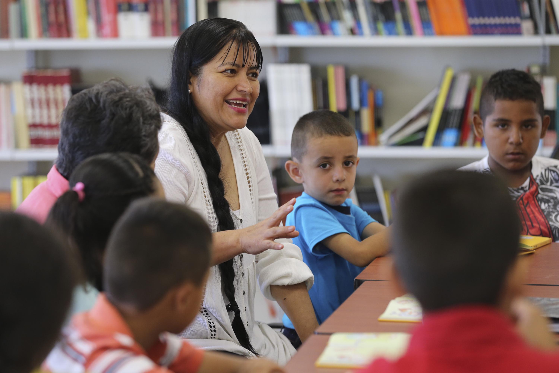 Mujer participante en programa, enseñando a niños en edad escolar primaria.