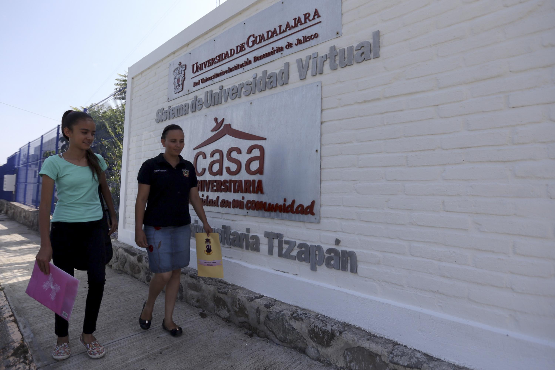 Trabajadora de UdeGVirtual portando un sobre con material de enseñanza y mujer adolescente pasando por las afueras de la Casa Universitaria de Tizapan.