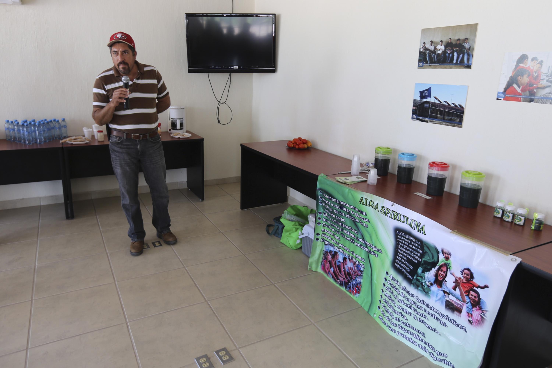 Participante en la Casa Universitaria de Tizapán el Alto, con micrófono en mano; explicando los beneficios del alga Spirulina, durante su exposición.