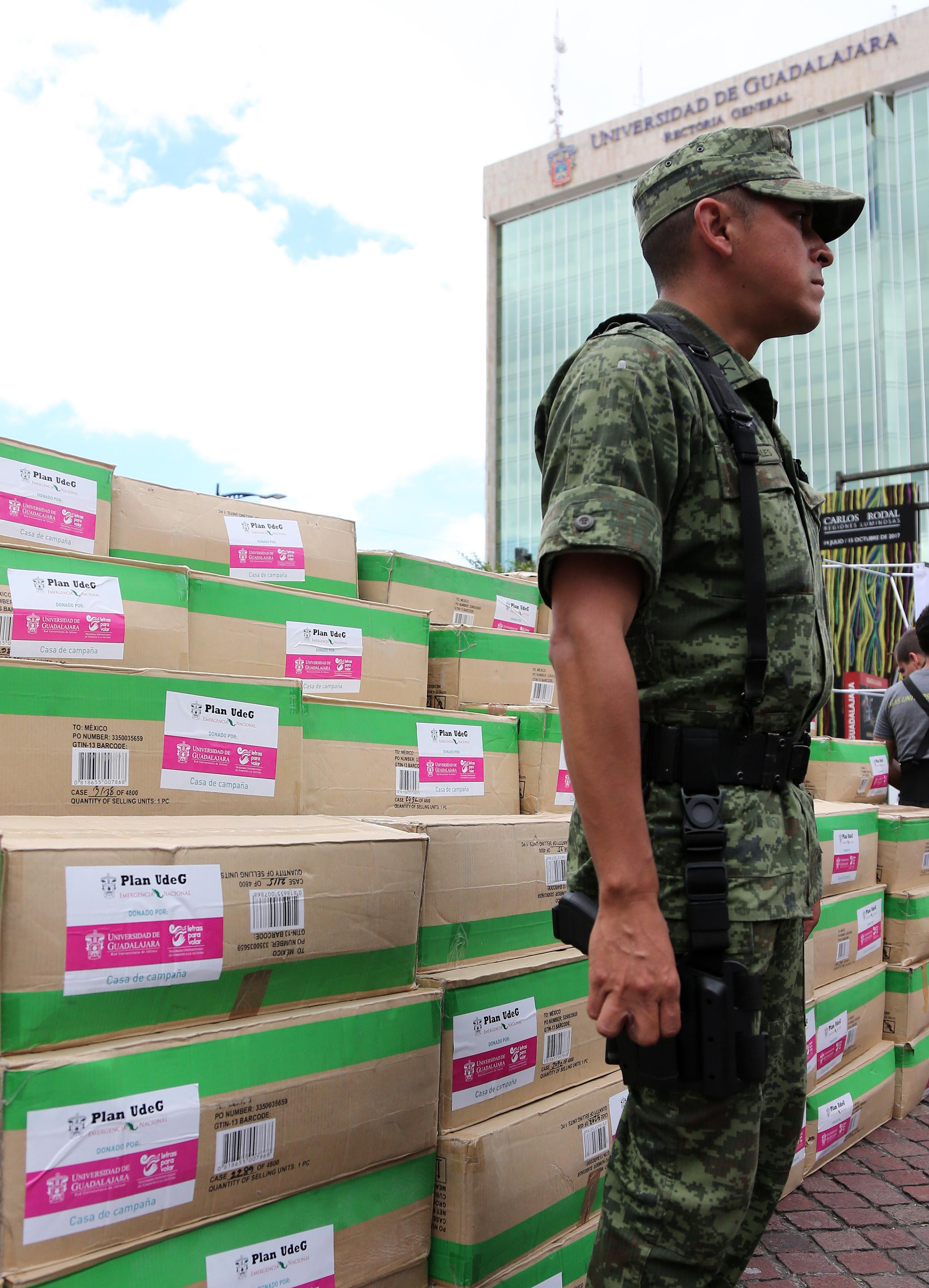 Militar resguardando víveres, donados por la comunidad universitaria y la sociedad de Jalisco, colectados en la Rambla Cataluña, uno de los principales centros de acopio de la universidad.