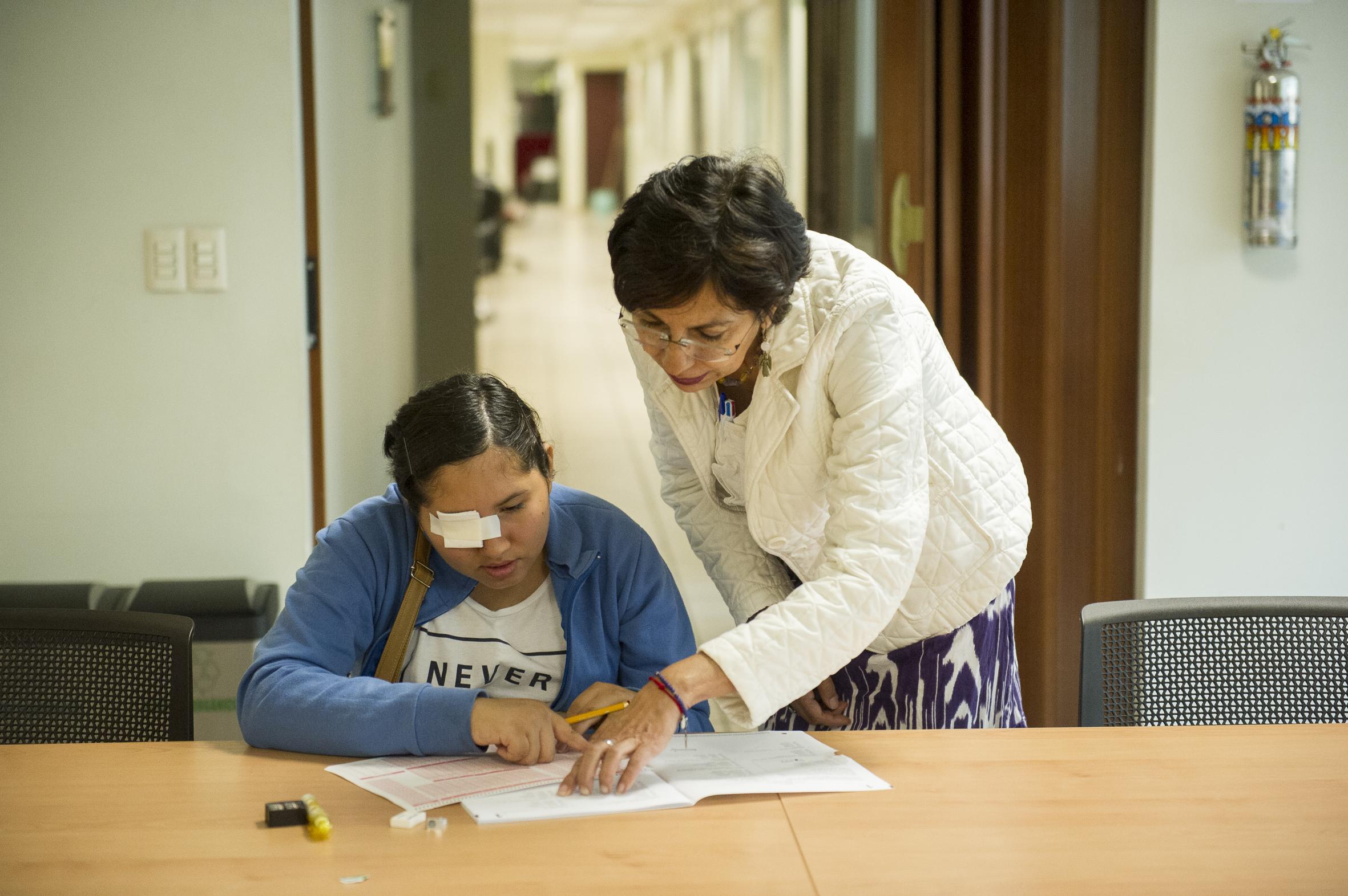 Instructor explicando las instrucciones y preguntas para entender el examen a aspirante en situación de discapacidad.