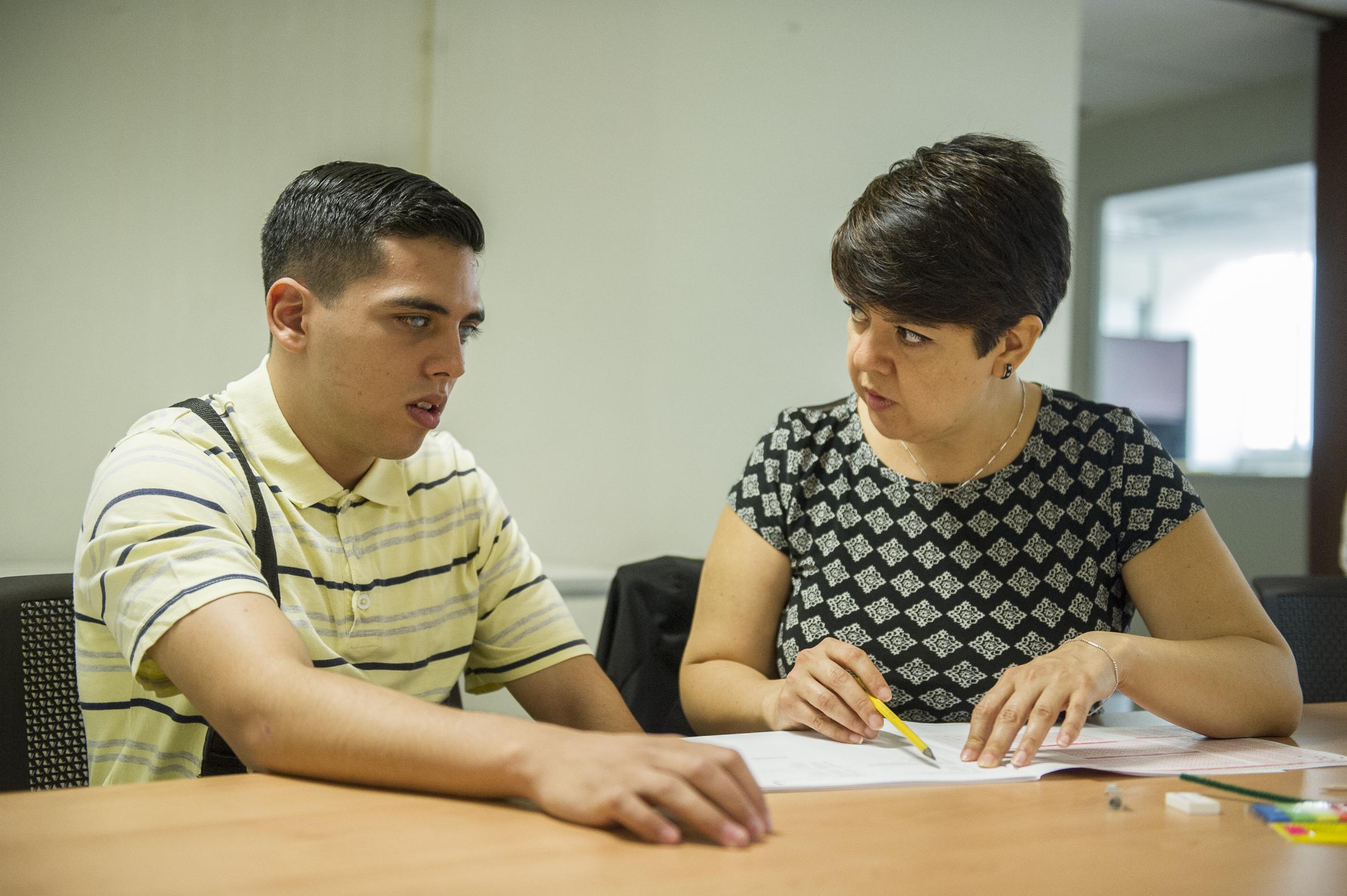 Instructor ayudando a leer para entender el examen a aspirante en situación de discapacidad.