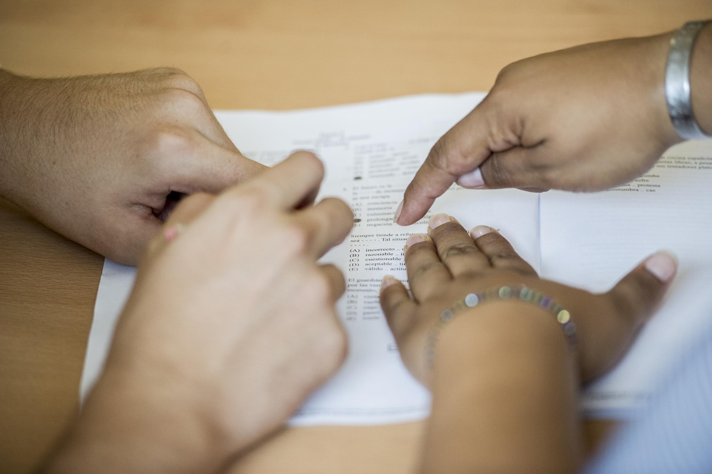 Instructor señalando con su dedo y explicando a aspirante en situación de discapacidad que debe de hacer en el examen.