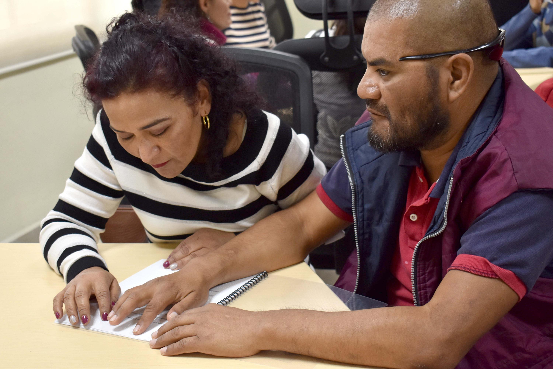 Profesora enseña el sistema Braille a persona con discapacidad visual