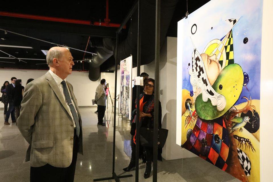 El Rector del CUValles, doctor Miguel Ángel Navarro, admirando uno de los cuadros de la exposición