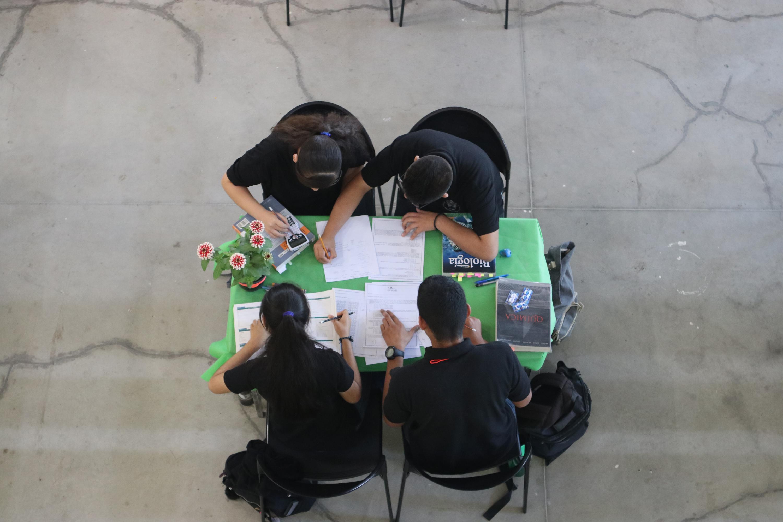 Grupo de cuatro estudiantes sentados participando en la Primera Eco Olimpiada SEMS-CUCEI,
